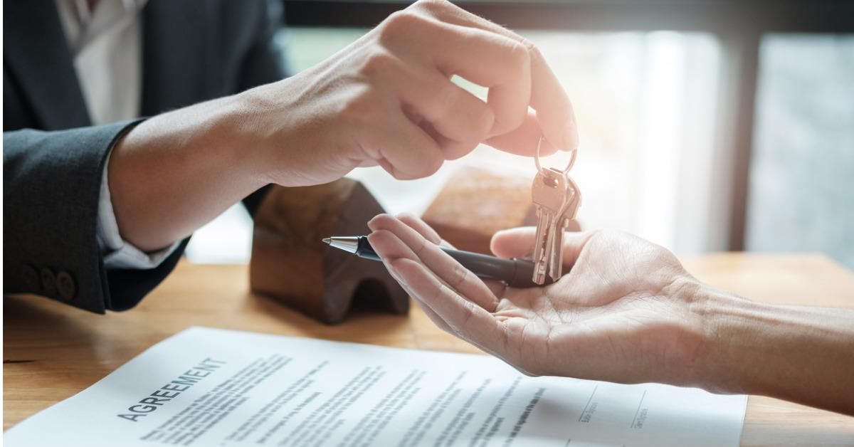 estate-agent-giving-house-keys-to-man-and-sign-agreement-in-office-picture-id803192850-1536098433445-1536098435269.jpg