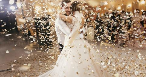 gorgeous-bride-and-stylish-groom-dancing-under-golden-confetti-at-picture-id1050000538-1552593117315.jpg