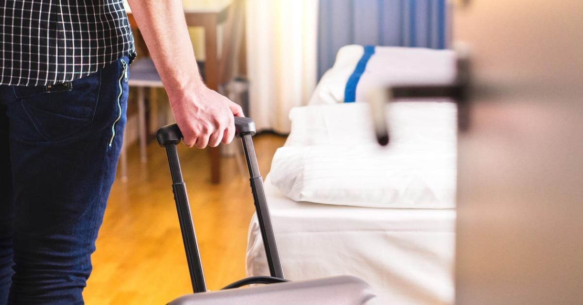 man-pulling-suitcase-and-entering-hotel-room-traveler-going-in-to-or-picture-id917609832-1542663440550-1542663442322.jpg