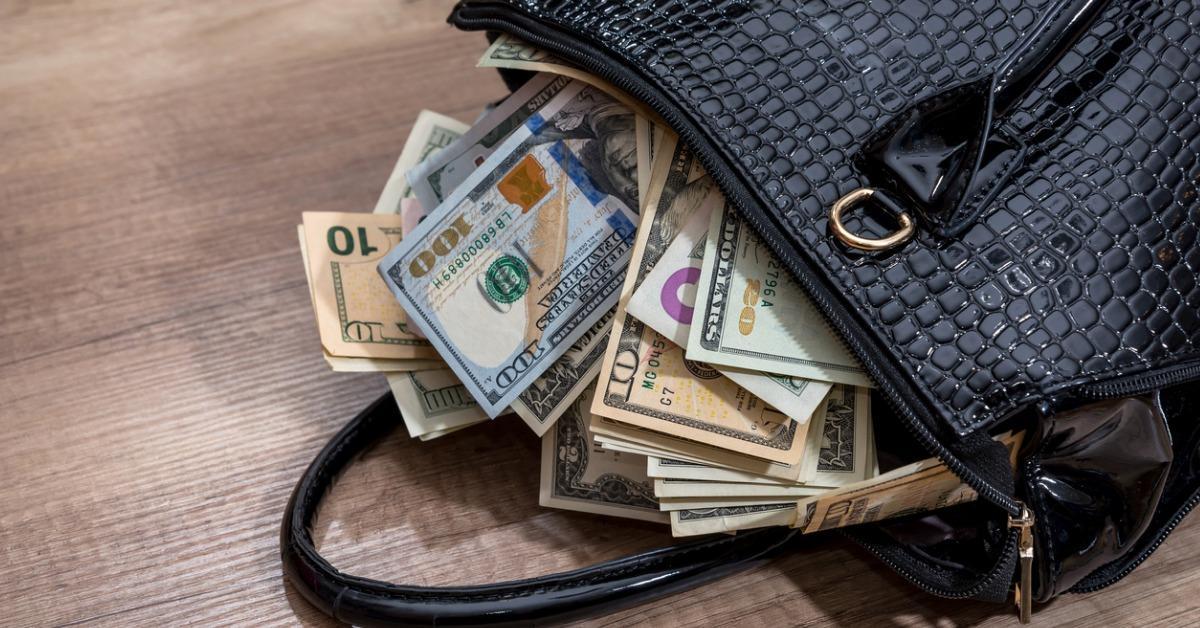black-woman-handbag-full-of-money-on-desk-picture-id651372658-1540495417344-1540495419024.jpg
