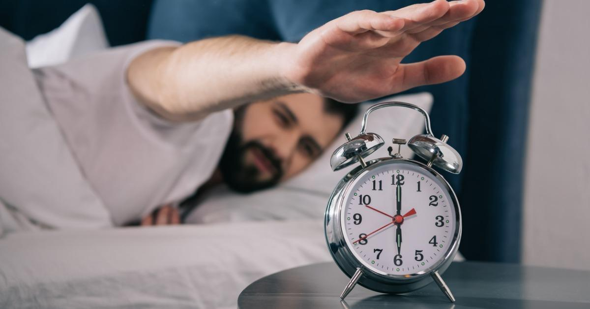 bearded-young-man-trying-to-turn-off-alarm-clock-while-lying-in-bed-picture-id811259254-1540407228934-1540407230755.jpg