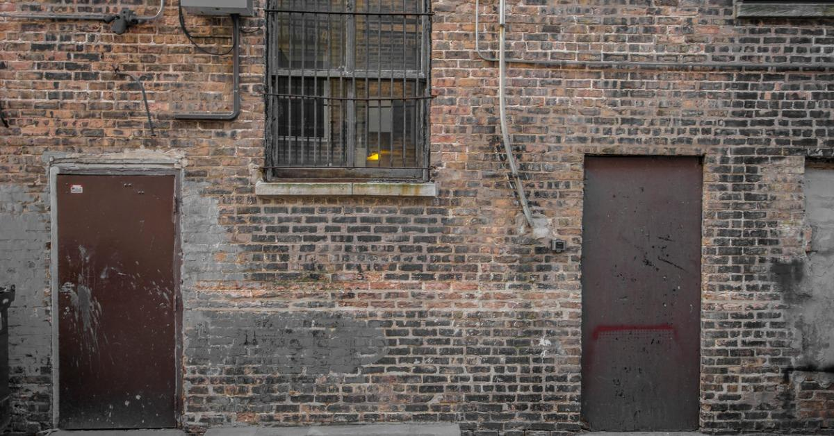 brick-wall-with-brown-doors-and-barred-window-picture-id911713826-1535729051731-1535729053445.jpg