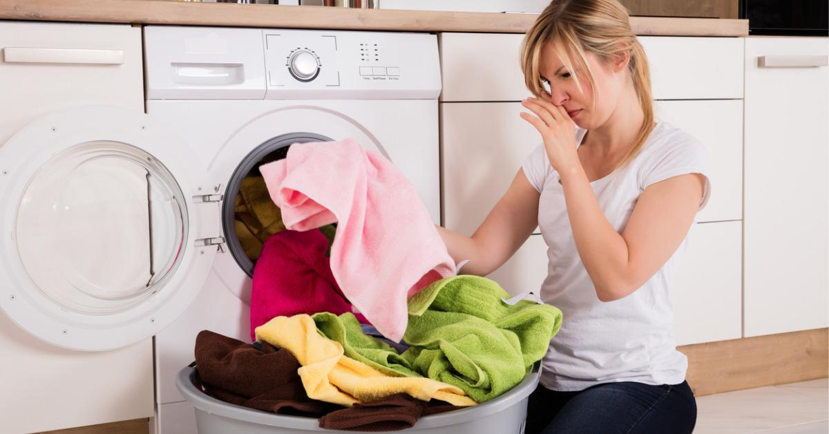 woman-unloading-smelly-clothes-from-washing-machine-picture-id859431472-1535053507814-1535053509442.jpg